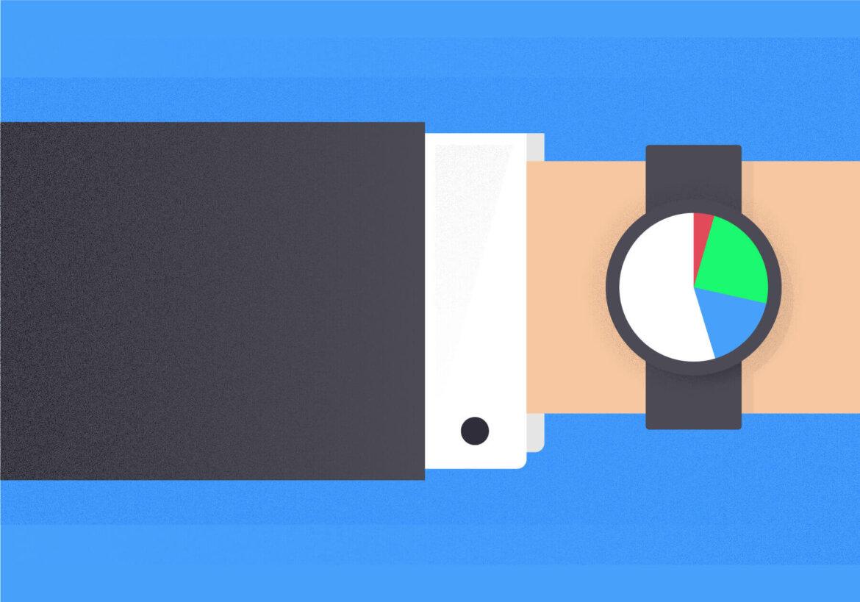 Ręka człowieka w garniturze, na nadgarstku zegarek przedstawiający kolorowy wykres kołowy.
